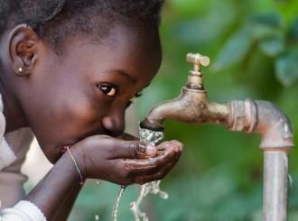 Jente drikker vann fra kran