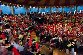 Publikum som holder grønne og røde stemmeskilt i været