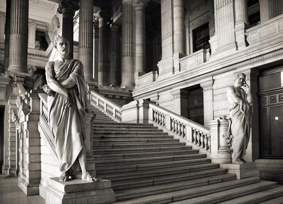 Monumental trappeoppgang innendørs, med skulpturer av filosofer i klassisk stil på begge sider
