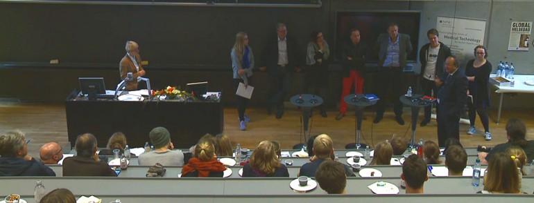 Bilde av panelteltakerne med publikum på benker i auditoriet