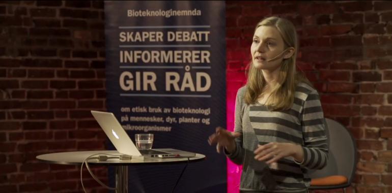 """Foredragsholder foran banner med teksten """"Bioteknologinemnda skaper debatt - informerer - gir råd"""""""