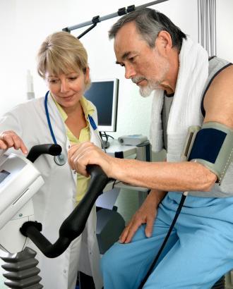 Lege sammen med pasient som sitter på ergometersykkel med måleytstyr rundt overarmen