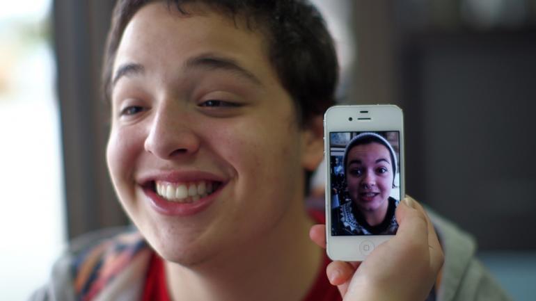 Ung gutt med bilde av jente på mobilskjerm