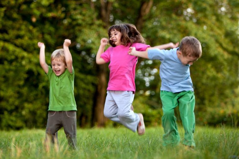 Tre barn som leker i gresset