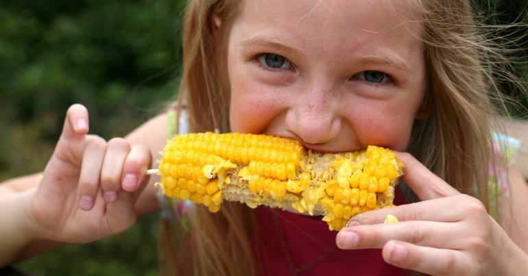 Jente spiser maiskolbe
