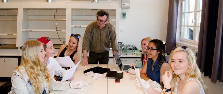 Seks elever og lærer rundt bord på naturfagrommet