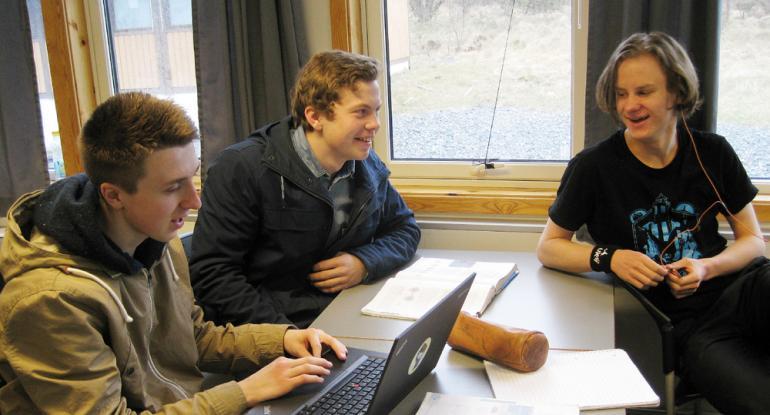 Tre gutter rundt pult med skolebøker, pennal og pc