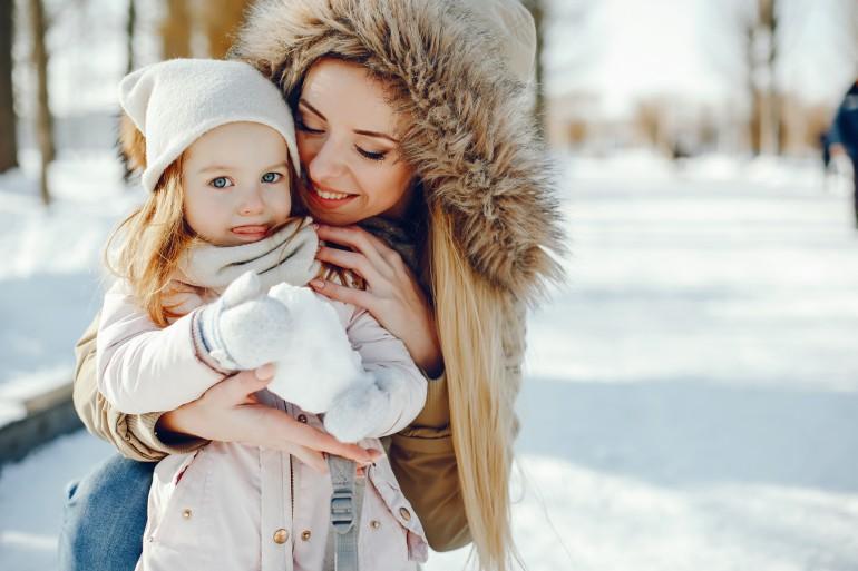 Bilde av mor og datter som leker ute i snøen.