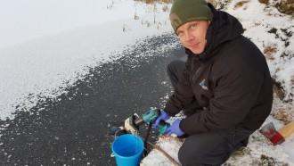 Bilde av Frode Fossøy fra NINA med måleutstyr i vannkanten. Vannet er dekket med is og snø.