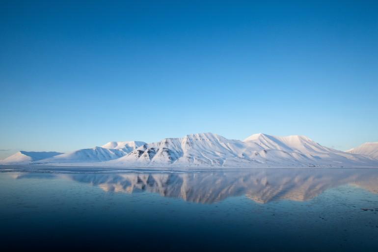 Bilde av Spitsbergen, Isfjord, vinterlandskap, snødekte fjell som speiles i havet.